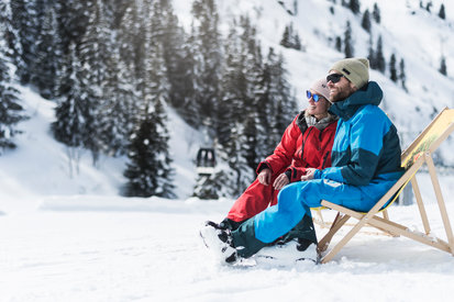 Skiers spend their time of break in the deck chair and enjoy the mountain panorama Galtür