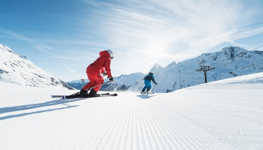 Skiers enjoy the well prepared slopes of the ski area Galtür on a sunny winter day