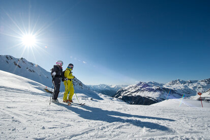 Skiers enjoy the stunning mountain panorama of Galtür at sunshine